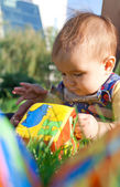 Baby lying in the grass and playing with blocks — Stockfoto