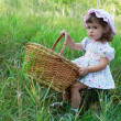 Little girl sitting on a stub and holding a basket — Stock Photo