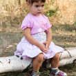 Stock Photo: Sad little girl sitting on log
