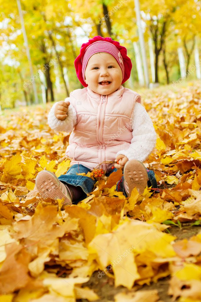 Laughing kid sits in an autumn park  Stock Photo #8630071