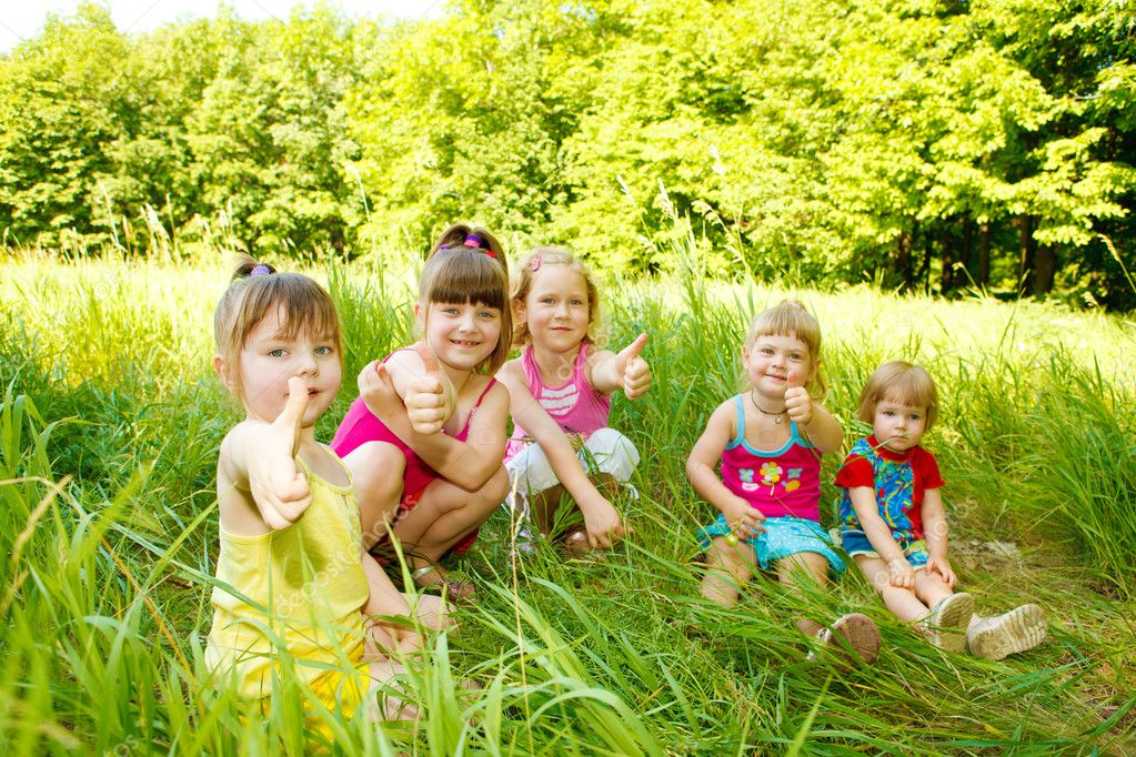 Group of five happy kids sitting in the grass — Stock Photo #8643980