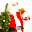 Stock Photo: Santa with present and christmas tree