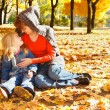 Mother and daughter in autumn leaves — Stock Photo #8653437