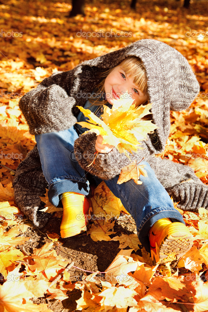 Lovely preschool girl sitting in an autumn park — Stock Photo #8653441
