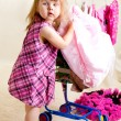 Girl putting clothing into trolley — Stock Photo