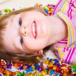 Kid lying among candies — Stock Photo