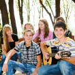 Teens crowd in park - Stock Photo