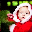 Baby decorating Christmas tree - Stock Photo