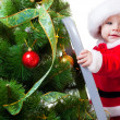 Baby in Santa costume on a step ladde - Stock Photo