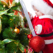 Baby decorating Christmas tree — Stock Photo