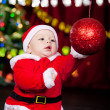 Baby playing with Christmas ball - Stock Photo