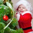 Baby decorating Christmas tree - Zdjęcie stockowe