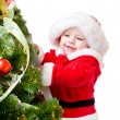 Baby decorating Christmas tree - Stok fotoğraf