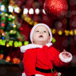 Kid looking at Christmas ball - Stok fotoğraf