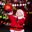 Baby catching Christmas ball - Stok fotoğraf