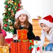 Kids sit beside Christmas presents — Stockfoto