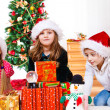 Kids sit beside Christmas presents - Stok fotoğraf