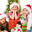 Kds sit beside Christmas presents — Stock Photo