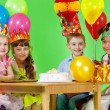Girls and boy in party hats and crowns — Stock Photo