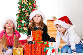 Kids sit beside Christmas presents — Stock Photo