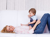 Mother lying playing with baby son — Stock Photo