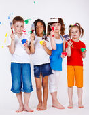 Kids holding paintbrushes and paints — Stock Photo