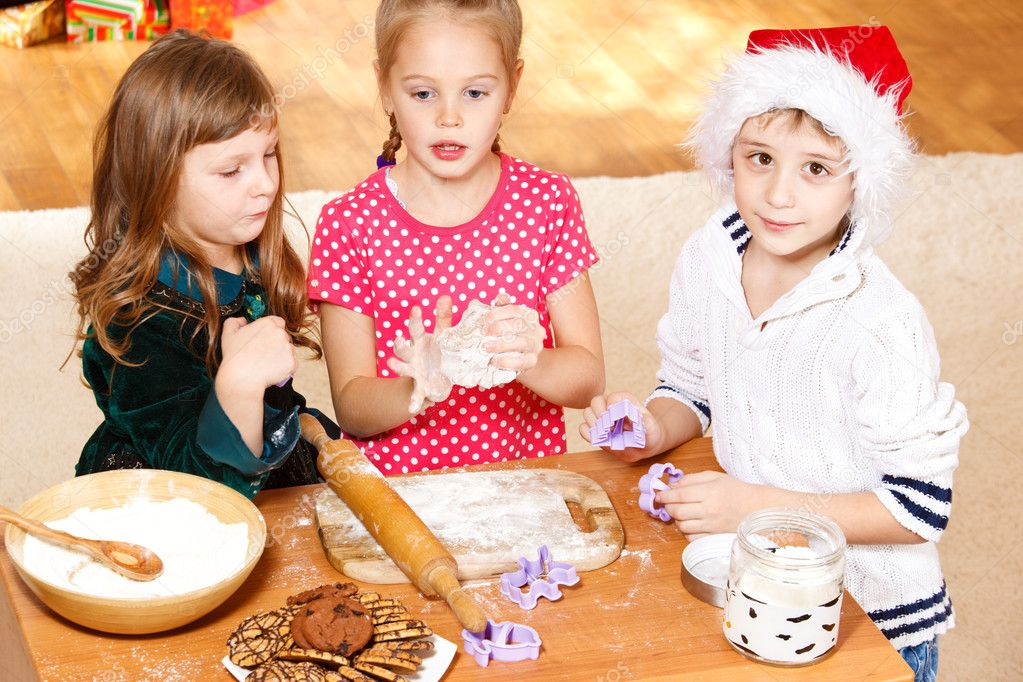 Three kids using dough cutters to make cookies — Stock Photo #8686496
