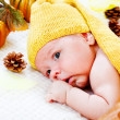 Infant among autumnal leaves and pumpkins — Stock Photo