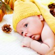 Infant among autumnal leaves and pumpkins — Stock Photo #8692065