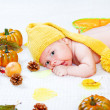 Baby amongst leaves and vegetables — Stock Photo