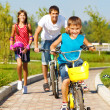 School aged boy and his father cycling — Stock Photo
