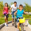 Stockfoto: School aged boy and his father cycling