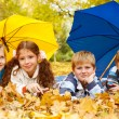 Kids group under umbrellas — Stock Photo