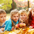 Joyful kids lying on autumnal leaves — Stock Photo