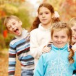 Kids stand one behind another - Stock Photo