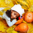 African american girl lying on pumpkin - Stock Photo