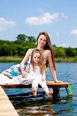 Mor och barn sitta på bron — Stockfoto