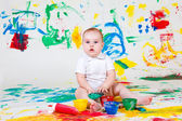 Curious baby playing with paints — Stock Photo