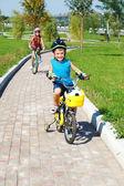 Um rapaz e sua irmã ciclismo — Foto Stock