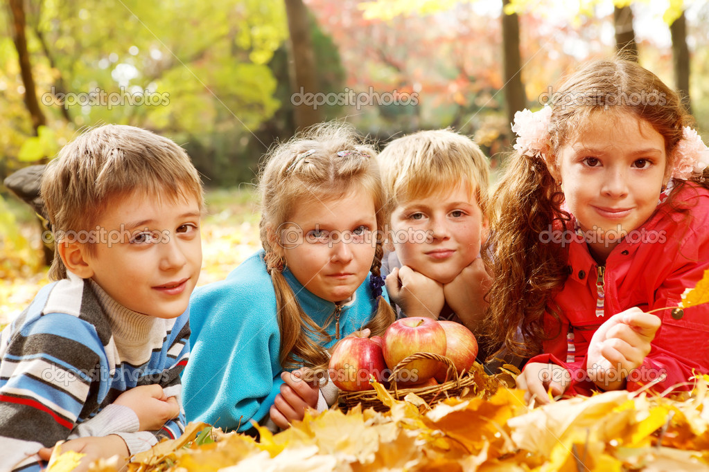 Joyful kids lying on autumnal leaves around apple basket — Stock Photo #8692824