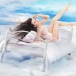 Brunette beauty lying on a bed in clouds — Stock Photo