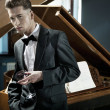Young pianist with glass of wine - Stock Photo