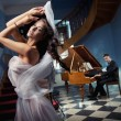 Sexy woman dancing to the piano music - Stockfoto