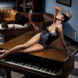 Stock Photo: Young sexy woman laying on a piano