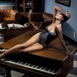 Young sexy woman laying on a piano - Stockfoto