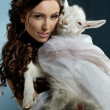 Cute brunette holding a little goat - Stock Photo