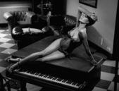Young sexy woman laying on a piano — Stock Photo