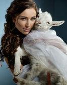 Cute brunette holding a little goat — Stock Photo
