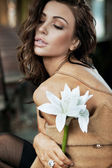 Brunette beauty posing with a flower — Stock Photo