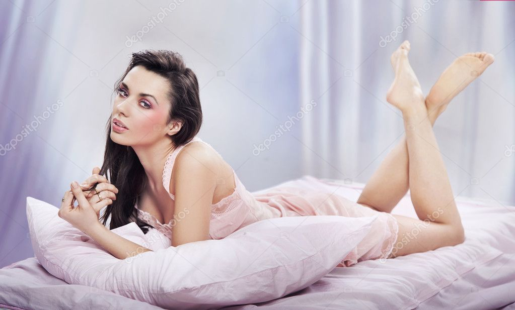 Adorable brunette posing on a comfortable bed — Stock Photo #10681784